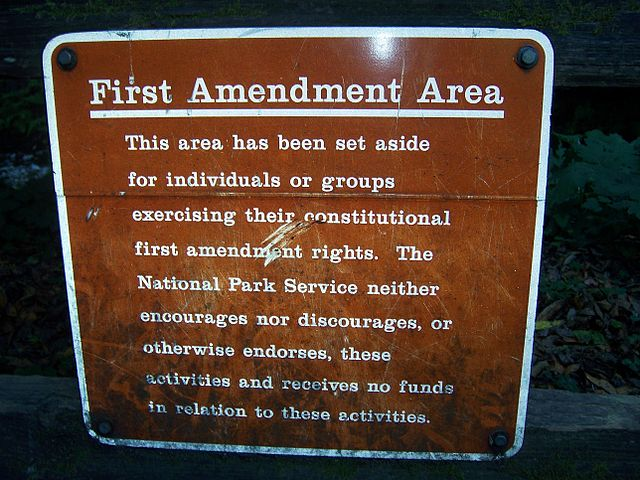 Picture of a sign from Muir Woods reading: 'First Amendment      Area: This area has been set aside for individuals or groups      exercising their constitutional first amendment rights. The      National Park Service neither encourages nor discourages, or      otherwise endorses, these activities and receives no funds in      relation to these activities.'