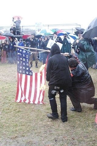 An altered American flag being burned during a protest.